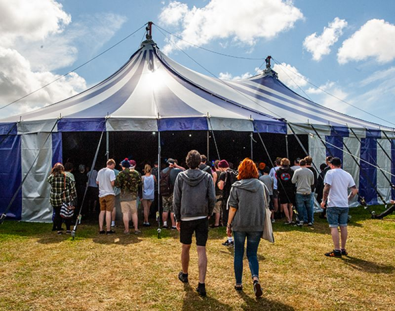 People walking into a busy blue and white striped festival tent