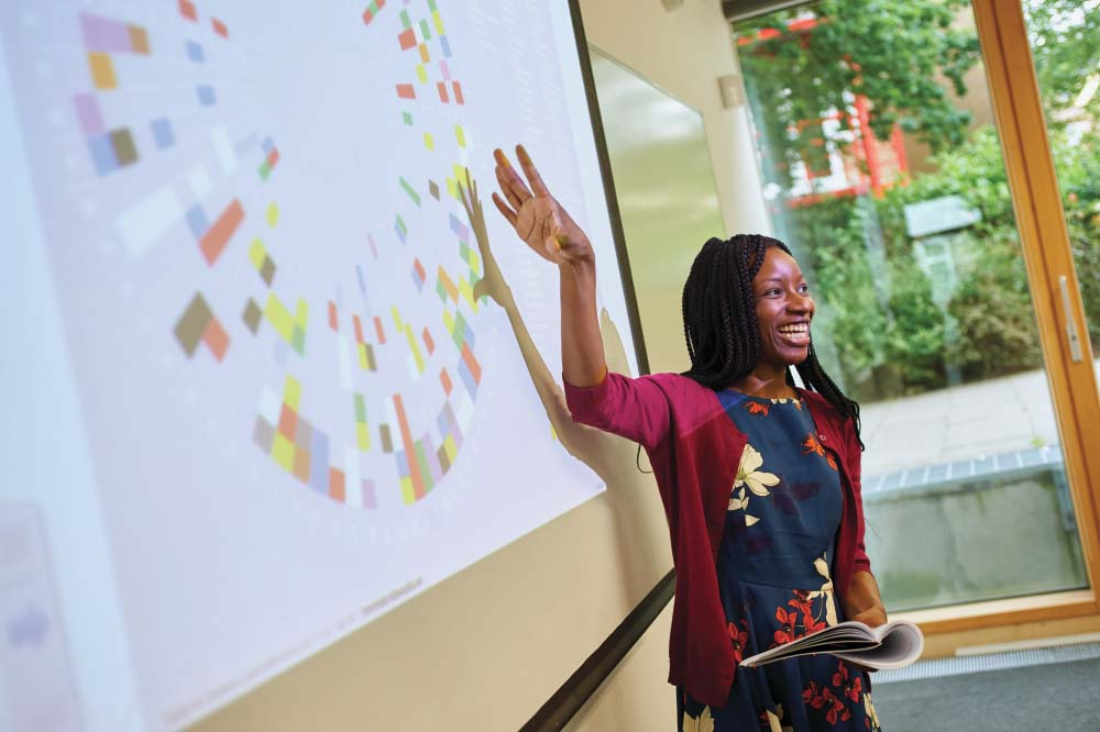 A black female lecturer stands in front of a projection on a whiteboard and smiles towards the room.